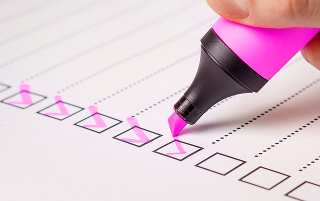 a highlighter ticking boxes on a checklist printed off on white paper