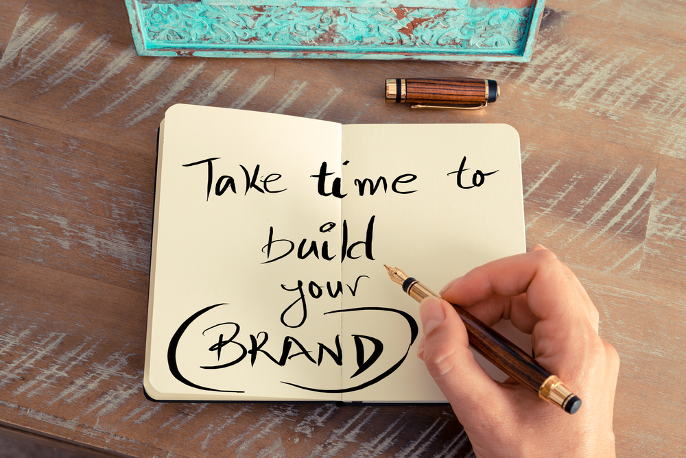 The words take time to build your brand written with a fountatin pen on paper