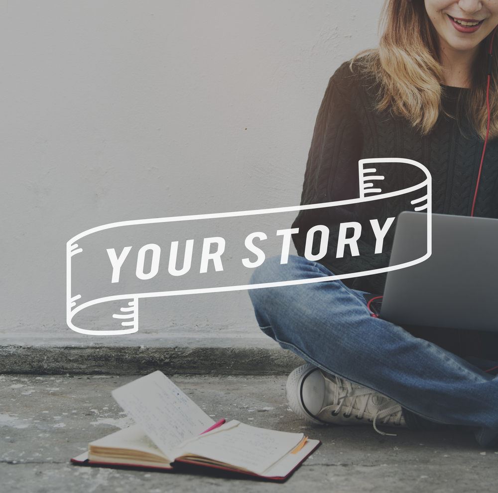 A girl sitting on a floor wearing jeans, trainers and brown top with a notebook and pen in front of her, a laptop on her lap and the words your story across the image