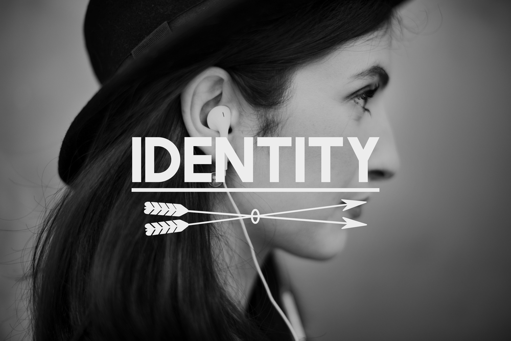 A black and white side shot of a woman with long hair wearing a hat ith the words Identity and two arrows underneath are dispplayed across the image